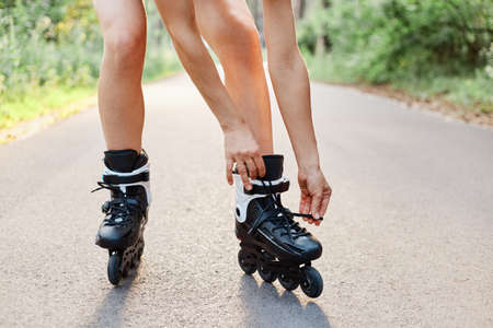 Faceless portrait of woman lace up roller skates while rollerblading outdoor in summer park on asphalt road, unknown female person rollerskating alone.