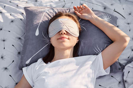 Outdoor shot of young brunette female wearing white casual style t shirt and sleeping mask lying on bed and sleeping, enjoying fresh air and sunshine.