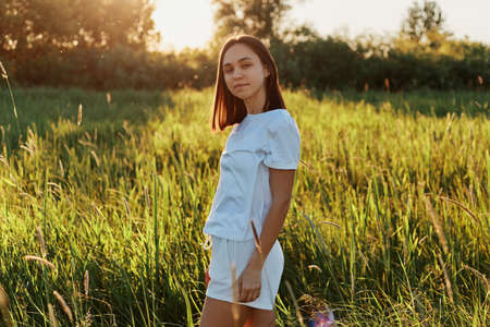 Outdoor shot of young adult beautiful woman wearing white clothes posing in the green meadow, standing and looking at camera, enjoying the beauty and tranquility of nature and the sunset. 版權商用圖片