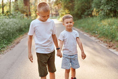 Two little boys wearing white t shirts and shorts going together and holding hands in summer park, brothers walking outdoor, expressing positive emotions. 版權商用圖片