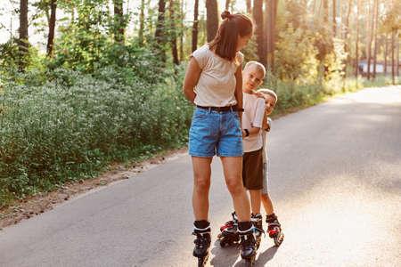 Mother with sons spending time together in summer park, family rollerblading, active pastime, children with mother roller skating outdoor on asphalt road. 版權商用圖片