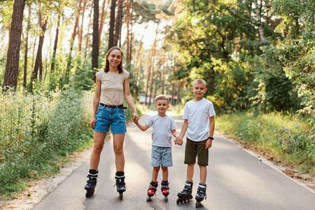 Outdoor shot of smiling attractive female with her little sons standing on road in summer park and holding hands, family rollerblading together, having fun, active pastime. 版權商用圖片