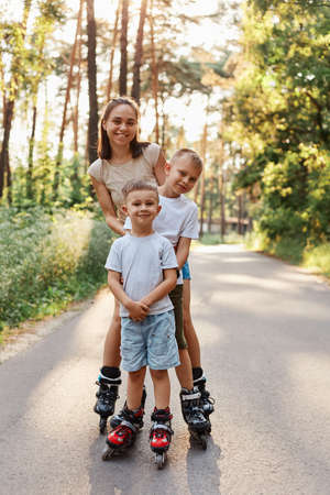 Happy family, dark haired female wearing casual attire standing with her sons outdoor, mother with children roller skating in park on asphalt road, having fun together.