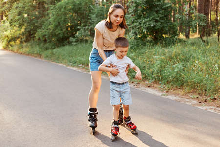 Full length portrait of woman and little son rollerblading together, mother teaching to roller skate his child, cute boy learning riding roller skates.