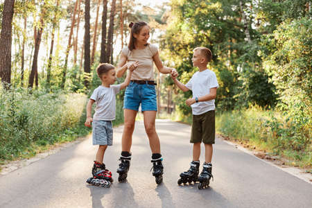 Outdoor shot of happy family having fun and roller skating together in summer park, mommy holding kids hands, being glad to spend weekend together, active pastime. 版權商用圖片