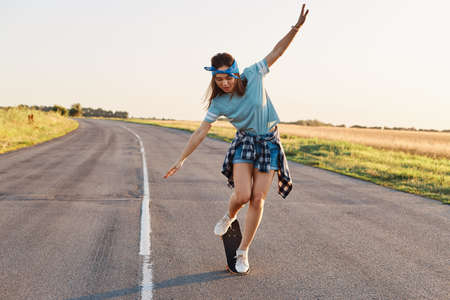 Full length portrait of slim sporty woman doing tricks on a skateboard, spending active time alone, outdoor on street, raised arms, looking down with excited facial expression.