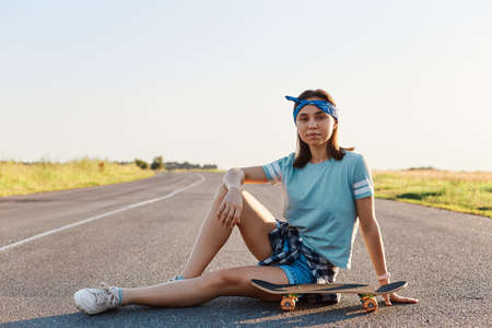Beautiful dark haired woman wearing t shirt, short and shoes sitting near surf skate on the asphalt road outdoor, relax and enjoy extreme surfskate in summertime.