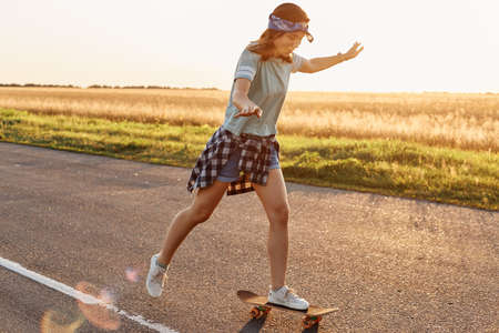 Side view of attractive slim sporty female wearing casual attire and hair band skateboarding outdoor alone in sunset, being happy to spend time in active way, summertime. 免版税图像