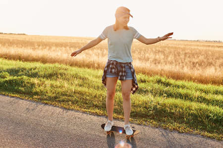 Full length photo of slim beautiful woman wearing casual clothing and hair band skateboarding on asphalt road on sunset, raising arms, enjoying active pastime.