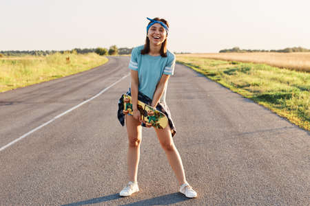Full length portrait of happy laughing female wearing casual t shirt, short and hair band, holding skateboard in hands and looking at camera, healthy lifestyle.
