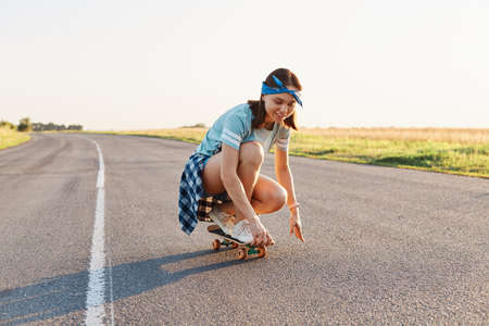 Portrait of happy beautiful dark haired female wearing casual attire and hair band surfing sitting on skateboard, having fun outdoor alone, healthy active lifestyle.
