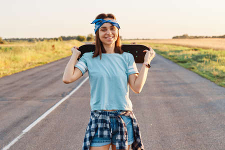 Outdoor portrait of happy dark haired female wearing blue t shirt, short and hair band, looking at camera with toothy smile, holding skateboard over shoulders, expressing happiness. 免版税图像