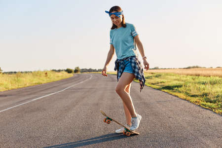 Full length photo of slim attractive woman doing tricks on a skateboard, having fun alone in the street, riding longboard, wearing casual clothing, looking down.