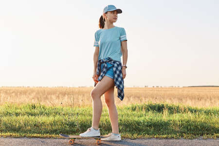 Full length portrait of slim sporty woman wearing t shirt and visor cap, standing with leg on skateboard and looking away, spending her leisure time in active way.