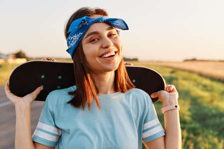 Outdoor shot of satisfied joyful female with dark hair holding skateboard over shoulders and looking directly at camera with toothy smile, enjoying skateboarding in summertime.