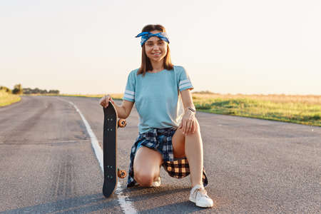Young adult smiling female with pleasant appearance squatting outdoor on asphalt road and holding skateboard, resting after riding, looking at camera with happy expression. 免版税图像