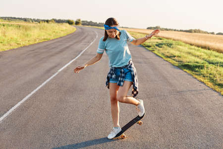 Outdoor shot of sporty woman in casual clothing having fun on asphalt road with skateboard, likes to spend time in active way, healthy lifestyle, happy pastime.