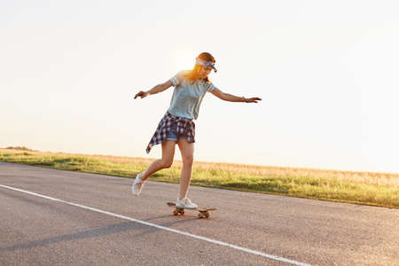 Young attractive female skater riding outdoor on asphalt road, raised her arms, sporty woman wearing casual clothing skateboarding alone in sunset in summer. 免版税图像