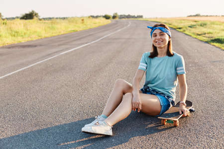 Photo of beautiful smiling female wearing t shirt, hair band and short, sitting on street with longboard, looking at camera with toothy smile, expressing happiness, enjoying leisure time.