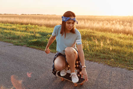 Young sporty woman wearing t shirt and hair band squatting on skateboard, riding longboard on asphalt road in summertime, spending sunset time in active way.