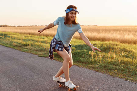 Outdoor shot of attractive female wearing casual style clothing riding skateboard on street, looking away with smile and concentrated expressing, being happy of her achievement.