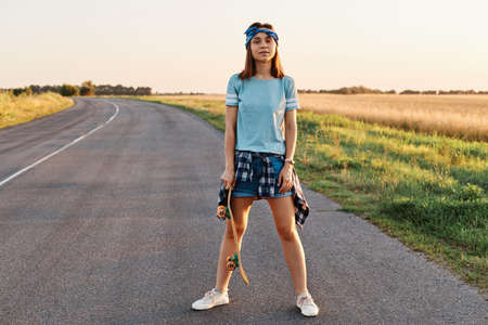 Full length photo of confident female wearing short, t shirt, hair band, holding skateboard in hands, looking at camera, after skateboarding outdoor.