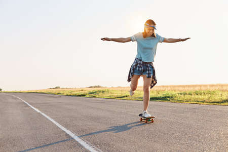 Full length photo of slim attractive happy female with positive emotions and toothy smile, riding skateboard in street, spending summertime in active way.