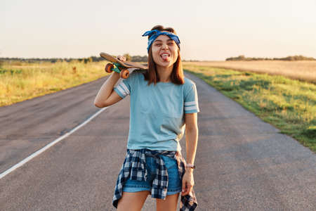 Happy positive female wearing t shirt, short and hair band holding skateboard on her shoulder, looking directly at camera with funny facial expression, grimace, showing tongue out.