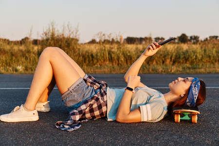 Dark haired young beautiful lady lay down on the asphalt road outdoor with hand on skateboard, using a mobile phone to take selfie or cheking social networks. 免版税图像