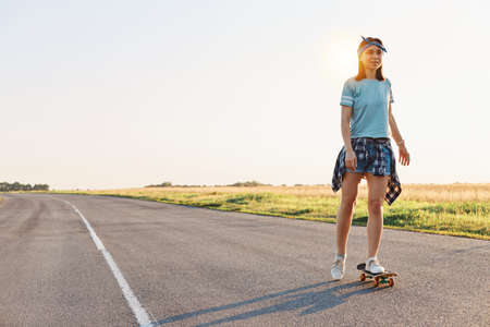 Beautiful female wearing t shirt, short and hair band skateboarding in the street, looking in distance, spending time alone with pleasure, active and healthy lifestyle.