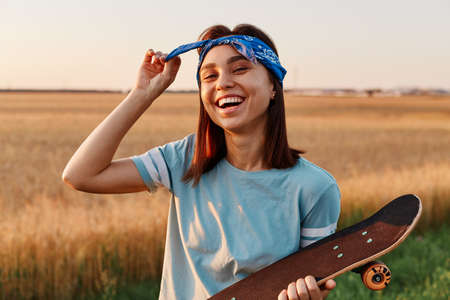 Portrait of happy laughing woman posing outdoor in summertime, holding skateboard in hands, touching her hair band, looking at camera with positive emotions.