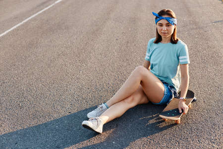Full length portrait of beautiful female wearing casual t shirt, short and hair band, sitting on asphalt road with skateboard, looking away with dreamily facial expression.