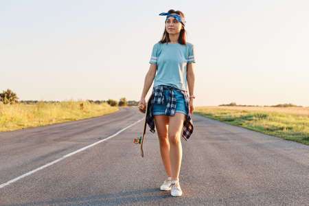 Positive attractive female wearing short, t shirt and hair band holding skateboard in hands and looking away, walking on asphalt road on sunset in summertime.