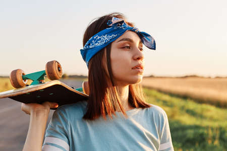 Pretty dark haired female wearing t shirt and hair band holding skateboard on her shoulder and looking away with pensive facial expression, resting after skateboarding.