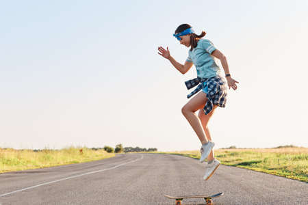 Sporty female wearing t shirt and short doing tricks on a skateboard on street on asphalt road, jumping in the air, enjoying skateboarding alone in sunset in summertime. 免版税图像