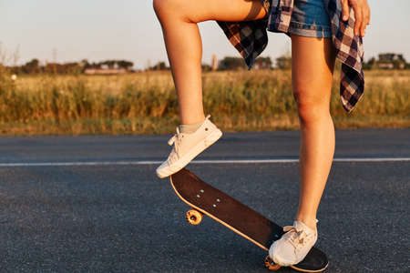 Unknown female person with long beautiful legs wearing white sneakers riding skateboard, faceless skater skateboarding in summertime, outdoor shot. 免版税图像