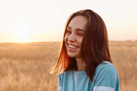 Summer portrait of laughing happy woman outdoor, enjoying warm sunshine, wearing blue t shirt, having dark hair, looking away with toothy smile, expressing happiness.