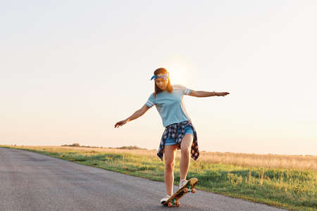 Full length shot of girl wearing casual attire skateboarding on empty street, spreading hands aside, enjoying riding, having concentrated facial expression. 免版税图像