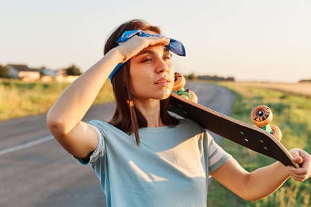 Photo of young adult brunette woman wearing casual style clothing looking far away, keeping palm near forehead, holding longboard over shoulder, waiting friends to skateboard together.