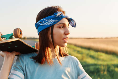 Side view portrait of pensive beautiful female wearing blue casual t shirt and stylish hair band, looking away with thoughtful look, holding skateboard over shoulders.