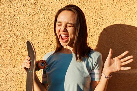 Photo of excited dark haired female wearing blue t shirt standing against yellow wall outdoor and screaming happily, holding longboard in hands, expressing happiness. 免版税图像