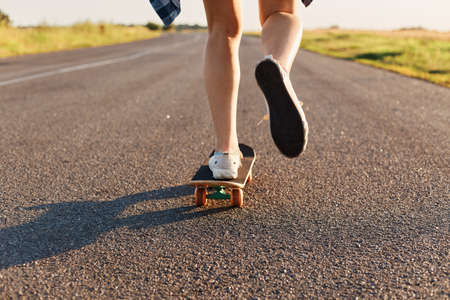 Unknown person wearing white sneakers riding skateboard on asphalt road, young woman legs skateboarding at street.