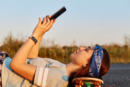 Side view portrait of slim beautiful woman wearing hair band and t shirt laying on asphalt road and keeping head on skateboard, holding phone in hands, making selfie or browsing internet.