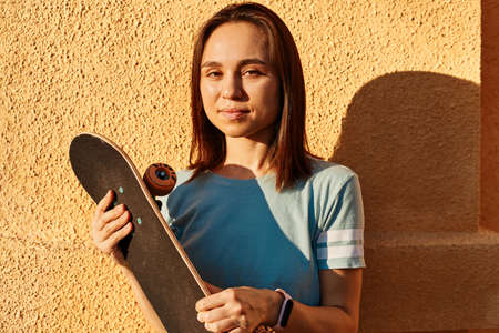 Outdoor portrait of happy dark haired female wearing t shirt posing isolated over yellow wall, looking art camera, holding skateboard in hands, summertime, sunset.