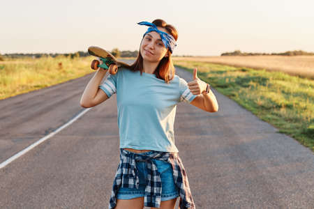 Cheerful girl with stylish hairband posing with a longboard over shoulders while walking on the road, looking at camera with happy emotions and showing thumb up.