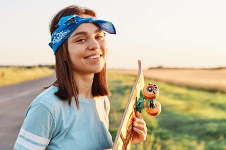 Outdoor shot of young adult winsome woman wearing blue casual style t shirt and hairband, standing with longboard in hands, looking at camera with charming smile.