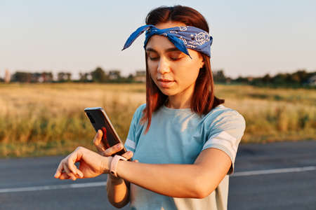 Young beautiful female fixing her armband before training with sunset on background. Attractive girl with preparing for workout, wearing hair band and casual style t shirt.