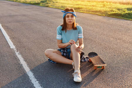 Young adult brunette woman sitting on asphalt road having trauma after falling down from the skate, having pain knee, looking at camera with frowning face. 免版税图像