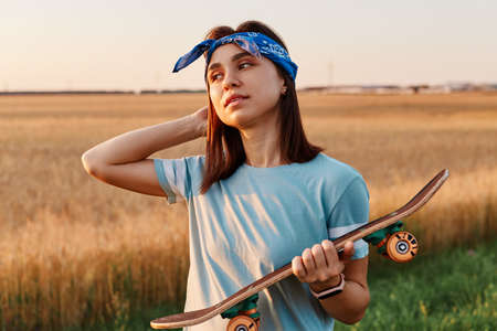Brunette female with pleasant appearance wearing blue t shirt and hairband, holding skateboard in hands, looking away, keeping palm on head, sunset in field. 免版税图像