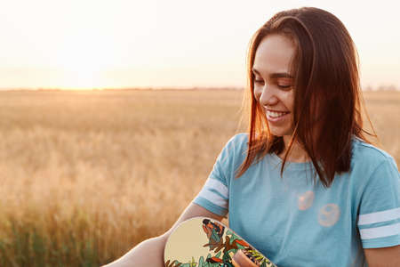 Extremely happy woman with dark hair wearing blue t shirt holding skateboard in hands, looking away, expressing positive emotions, posing with field and sunset on background.